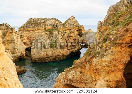 Stone arches, caves, rock formations at Dona Ana Beach (Lagos, Algarve coast, Portugal) in the evening light.  - stock photo