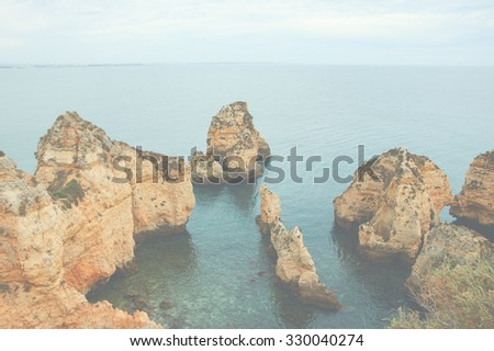 Stone arches, caves, rock formations at Dona Ana Beach (Lagos, Algarve coast, Portugal) in the evening light. Toned photo with haze. - stock photo
