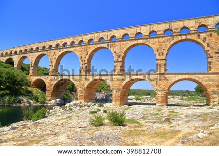 Stone arches of Pont du Gard aqueduct crossing a river near Nimes, France - stock photo