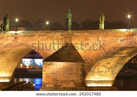 Stone arches of the Charles bridge illuminated in autumn night, Prague, Czech Republic - stock photo