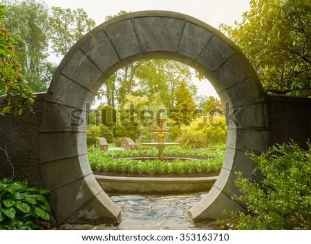 Stone archway in flower garden - stock photo