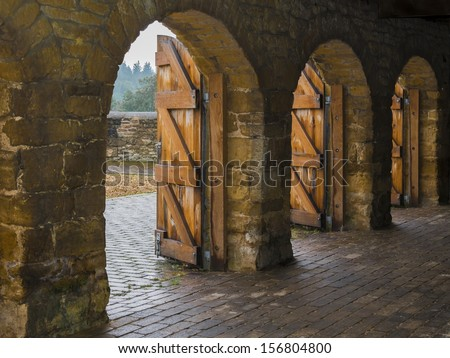 Stone archways with open wooden doors - stock photo