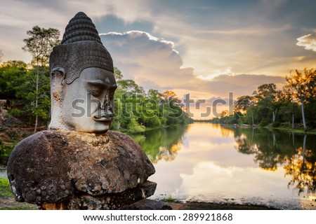 Stone Asura on causeway near South Gate of Angkor Thom in Siem Reap, Cambodia. Beautiful sunset over ancient moat in background. Mysterious Angkor Thom is a popular tourist attraction. - stock photo