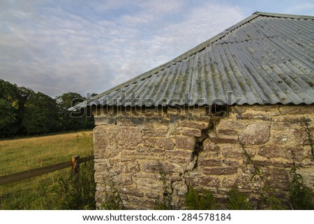 stone barn in field with corrugated metal roof