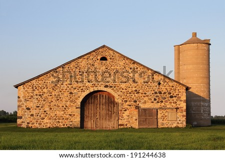 Stone Barn - Old stone barn in warm sunlight. - stock photo