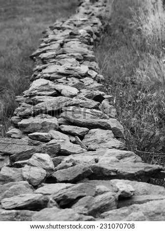 Stone barrier in a meadow. Brittany, France. Selective focus. Boundary concept. Aged photo. Black and white. - stock photo