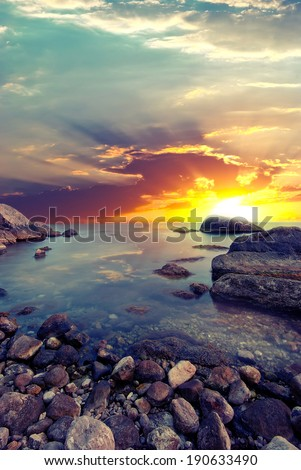 Stone beach and the sun setting behind the stone. Vintage style - stock photo