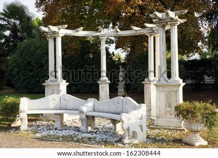 Stone bench and columns centre a peaceful Mediterranean garden - stock photo