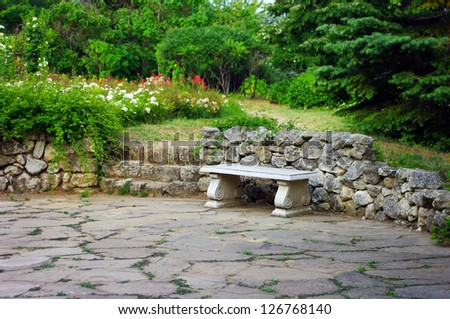 Stone bench in the garden - stock photo
