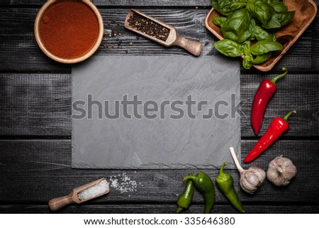 Stone board with different spices on wooden surface - stock photo