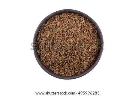 Stone bowl and pile of cumin seeds isolated on white background
