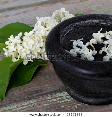 Stone bowl with a bouquet of white lilac spring flowers on wooden background - stock photo
