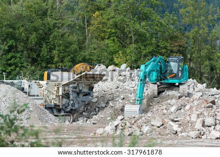 stone breaker and shovel digger on demolition site - stock photo