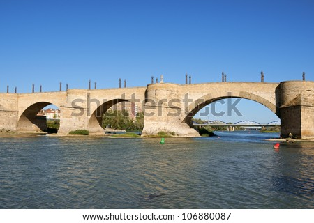 Stone Bridge (Puente de Piedra) over river Ebro in Zaragoza, Spain. It is also called Lion Bridge because 2 couples of bronze lions on pillars are placed at each side of the bridge.