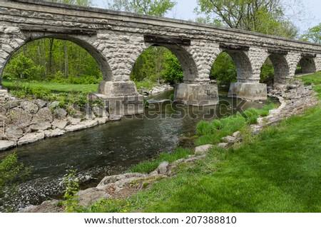 Stone bridge with arches crossing waterway - stock photo
