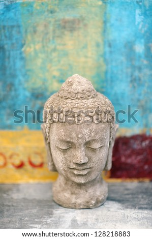 Stone Buddha head sculpture photographed in studio.