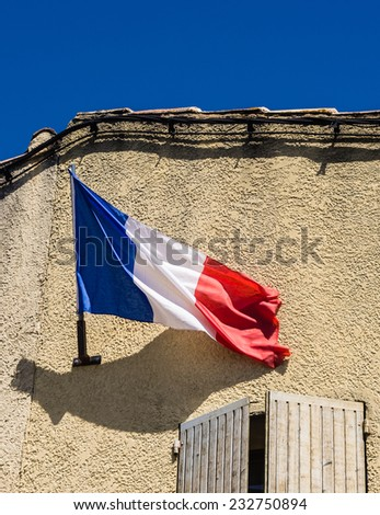 Stone building with french facade flag and window shutters.