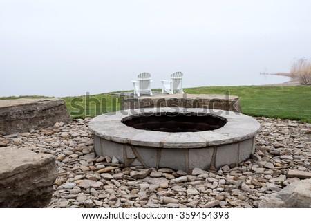 Stone campfire at cottage lake with muskoka and adirondack chairs - stock photo