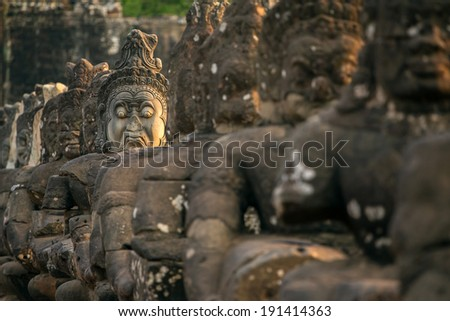 Stone carved statues of Asuras on the bridge to Angkor Thom in Angkor complex, Siem Reap, Cambodia