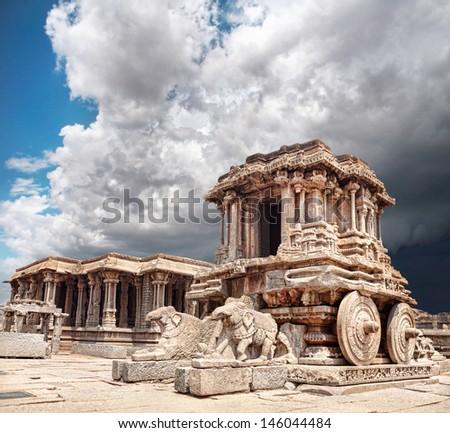 Stone chariot in courtyard of Vittala Temple at blue overcast sky in Hampi, Karnataka, India - stock photo