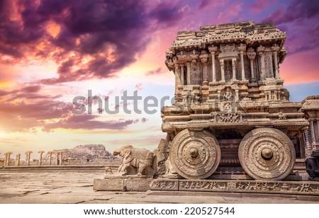 Stone chariot in courtyard of Vittala Temple at sunset purple sky in Hampi, Karnataka, India - stock photo