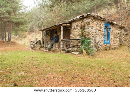 Stone Cottage In A Forest With Young Man Sitting Down On The Porch