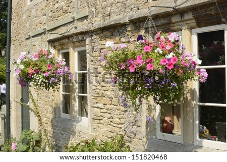Stone cottage with hanging flower baskets in front of windows. Wiltshire. England - stock photo