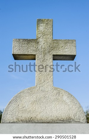 Stone cross against blue sky in a cemetery - stock photo