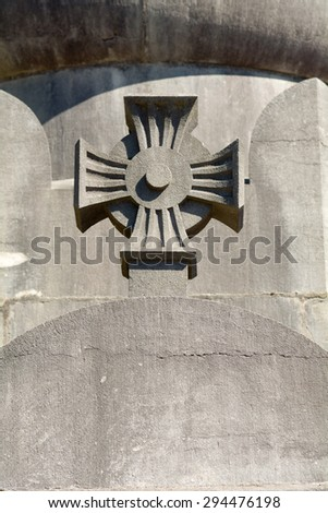 Stone cross carved into tomb in cemetery  - stock photo