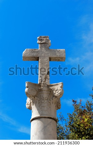 Stone Cross on a Column / Stone cross with INRI inscription on a marble column in Corinthian style on blue sky. Bonassola, Liguria, Italy - stock photo