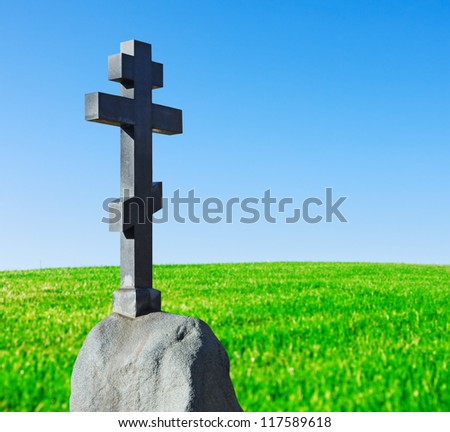 stone cross on a pedestal stands in a field in a landscape - stock photo