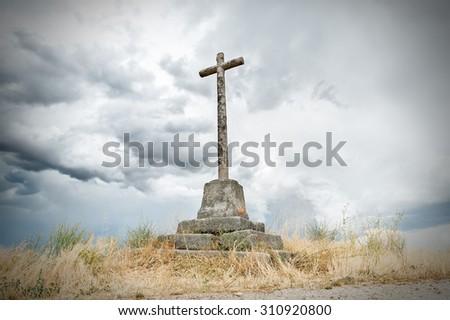 stone cross on dark sky background with - stock photo