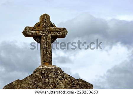 Stone cross on gravestone against blue cloudy sky at a cemetery.