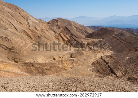 Stone desert mountains cliffs near Eilat Red sea bay, dry riverbeds canyons gorges, Negev desert, Israel.