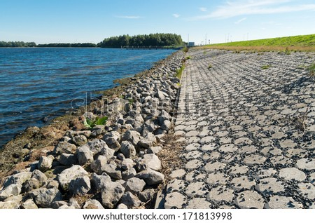 stone dike along a lake in the netherlands - stock photo