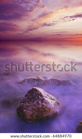 Stone during sundown in sea water - stock photo