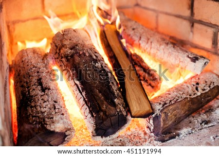 stone fireplace with burning firewood - stock photo