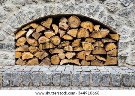 stone fireplace with firewood without fire - stock photo