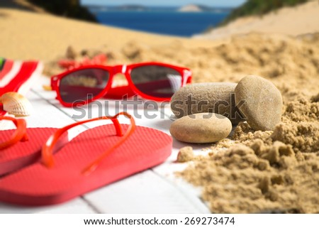 Stone^ flip flop and sunglasses on sandy pier near ocean - stock photo