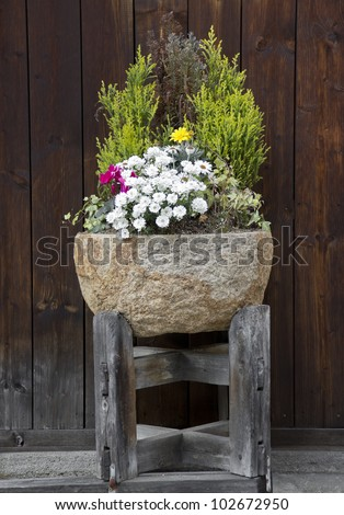 Stone flower pot with nice arrangement of plants and flowers - stock photo