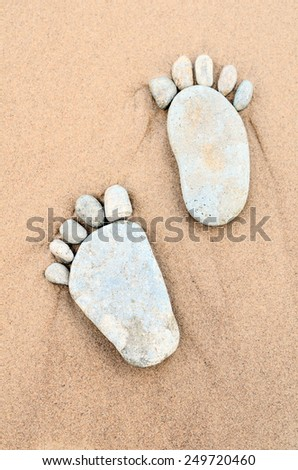 Stone footprints in the sand - stock photo