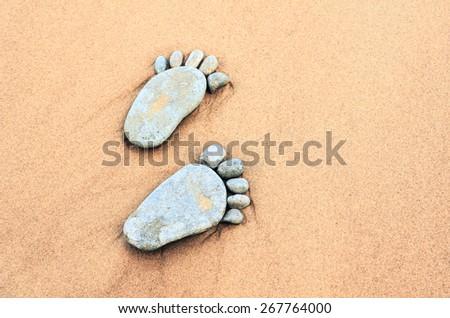 Stone footprints in the sandy beach - stock photo