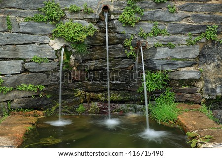 stone fountain with three jets of water falling - stock photo