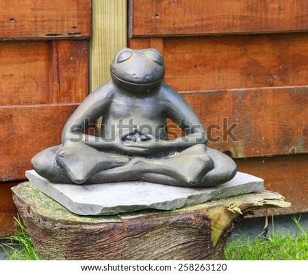 Stone garden frog meditating sitting on a tree trunk - stock photo