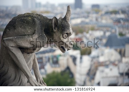 Stone gargoyle (Chimera) overlooking the city of Paris from the tower of the Notre Dame - stock photo