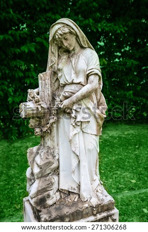 Stone gravestones statue on old classical in cemetery in green park - stock photo