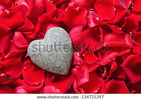 stone heart in red rose petals