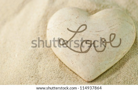 Stone heart in sand. - stock photo