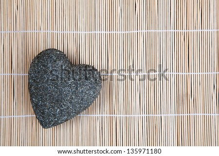 stone heart on a bamboo mat