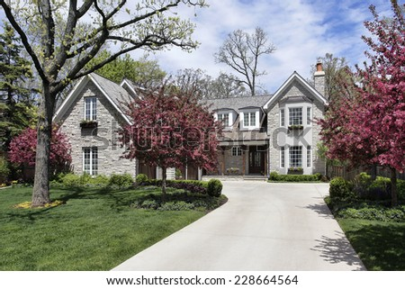 Stone home in suburbs with flowering trees - stock photo